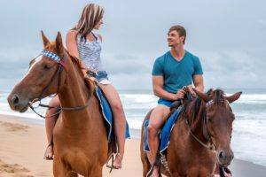 Romantic Couple on horses at beach