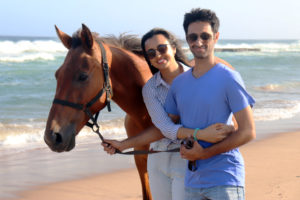 Couple hugging with horse on beach