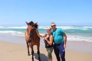 Couple standing next to horse on beach