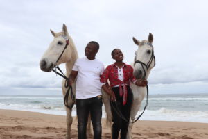 Couple with white horses on the beach. Romantic memories for a lifetime